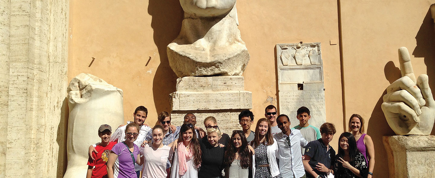 Students in Rome, Italy by large statues